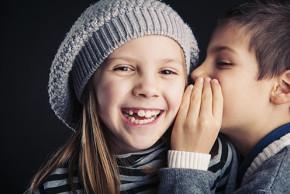 Enfant qui chuchote dans l'oreille d'une autre enfant