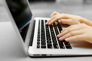 Femme qui tape sur le clavier d'un ordinateur
